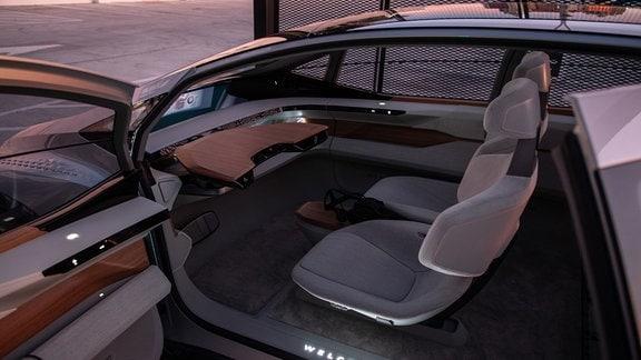 Blick ins Cockpit des Konzeptfahrzeugs Audi AI:ME (2019) mit einem futuristischen Design aus rauem Stoff und Holzelementen.