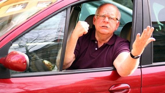 Ein Autofahrer schimpft aus dem geöffneten Fenster heraus.