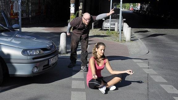 Symbolbild:Agressionen im Straßenverkehr - Ein wütender Autofahrer versucht eine konzentrierte, mitten auf der Straße sitzende Yogafrau zu vertreiben.