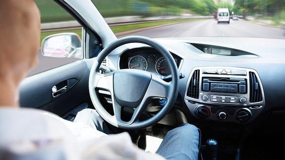 Ein Mann sitzt im Auto und fährt mit Autopilot