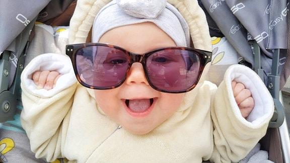 Baby mit einer Sonnenbrille für Erwachsene
