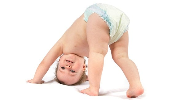 Ein Kleinkind mit einer Windel mit dem Kopf auf dem Boden