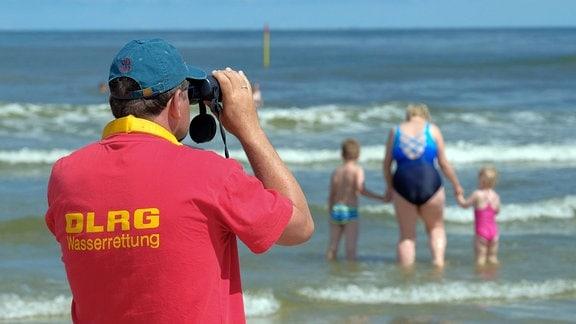 Mitglied der DLRG Wasserrettung steht am Strand der Insel Spiekeroog und beobachtet Schwimmer in den Wellen der Nordsee.