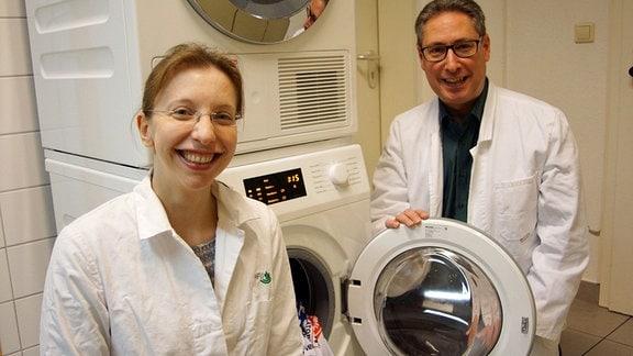 Die Wissenschaftler Susanne Jacksch und Markus Egert von der Hochschule Furtwangen zeigen das Bullauge einer Waschmaschine (Frontlader).