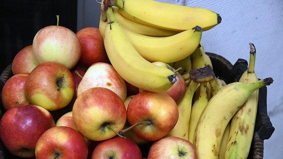 Äpfel und Bananen in einem Obstkorb.