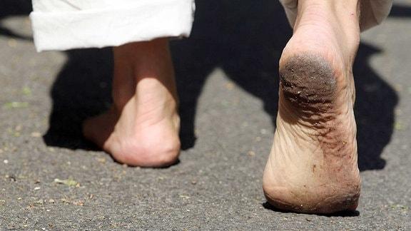 Ein Mann läuft barfuß.
