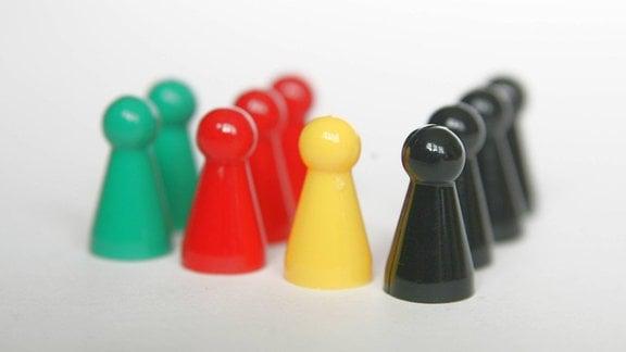 Spielfiguren in den Farben grün. rot, gelb und schwarz