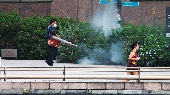 Ein Mann versprüht Pestizide