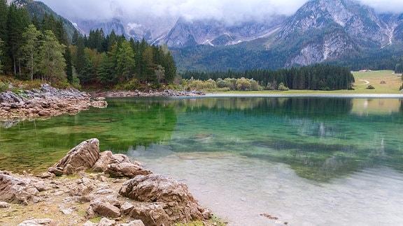 Idyllischer Bergsee mit klarem, türkisfarbenem Wasser, Geröll im Vordergrund, Nadelbäume am Ufer sowie hochalpinen Bergen im Hintergrund