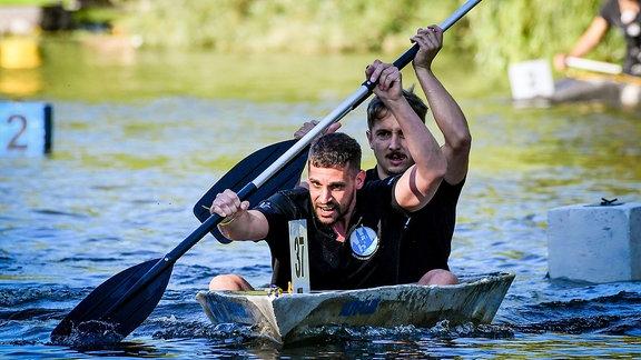 Zwei Männer paddeln in einem Betonkanu