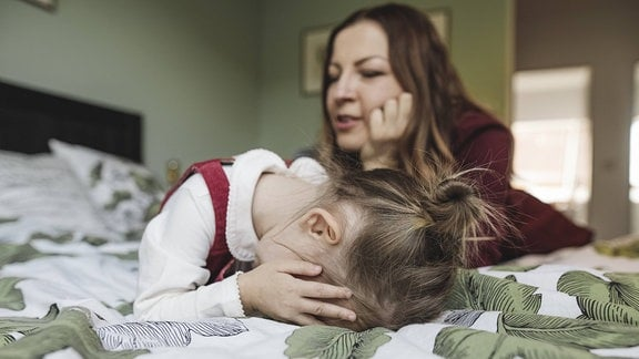 Eine Frau und ein Mädchen, das sich die Augen zuhhält, liegen auf einem Bett.