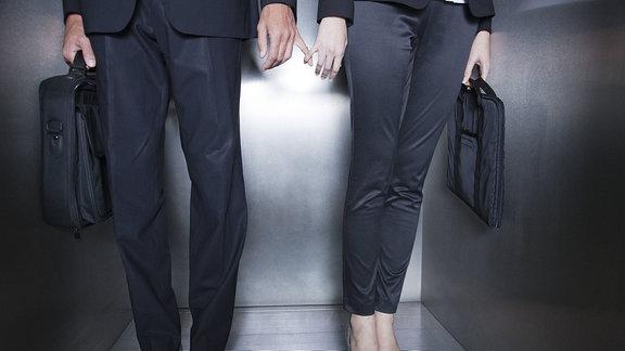 Eine Frau und ein Mann (nur Oberkörper und Beine zu sehen) in formeller Berufskleidung stehen in einem Aufzug und berühren sich unauffällig mit den Fingern.