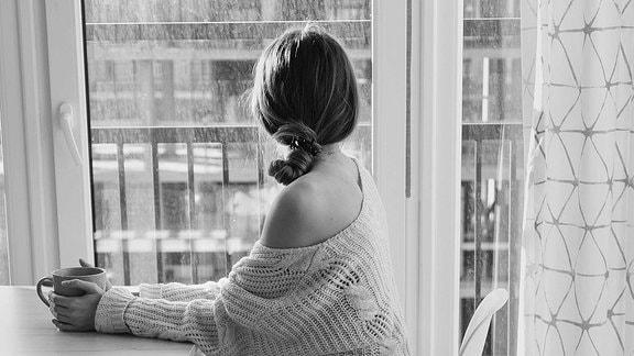 Eine Frau sitzt alleine an einem Fenster und schaut hinaus