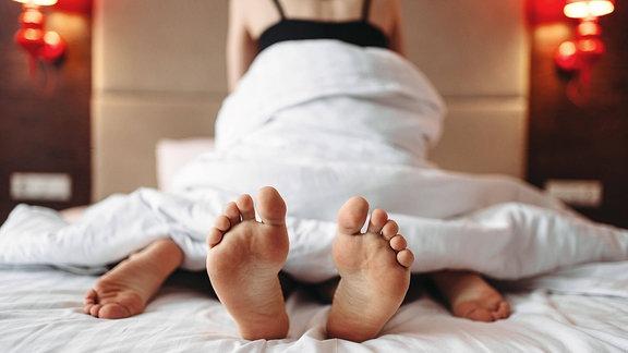 Zwei Personen übereinander in einem Bett, Ansicht vom Fußende aus, bedeckt mit Decke, unscharf im Hintergrund Oberkörper einer Frau mit Top.