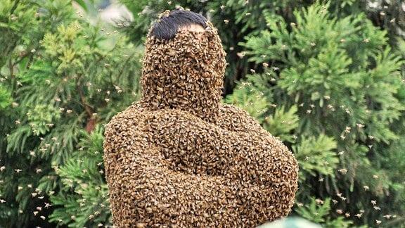 Ein Mann mit Bienen bedeckt.