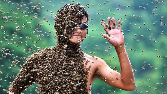Der Körper eines jungen Mannes ist fast vollständig mit Bienen bedeckt