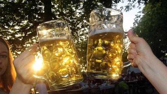 Zuprosten mit zwei Maßkrügen Bier in der Abendsonne