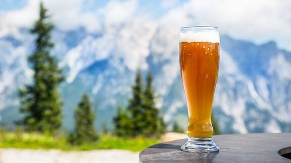 Ein Glas Bier vor einer Bergkulisse