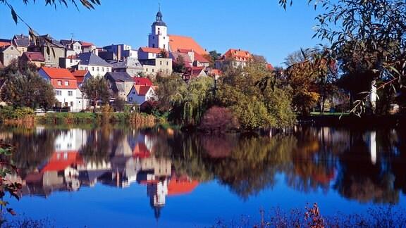 Die Silhouette von Ronneburg mit St Marien Kirche über dem Bader-Teich in Thüringen