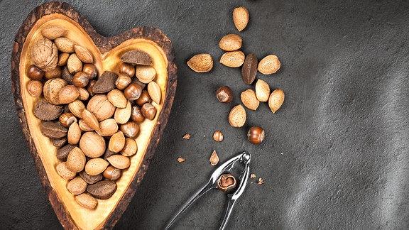 Nüsse liegen in einer herzförmigen Holzschale, daneben liegt ein Nussknacker