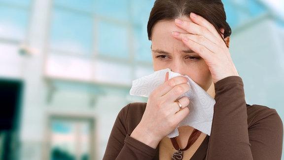 Eine Frau hält sich ein Taschentuch an die Nase.