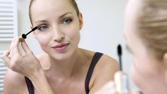 Eine junge Frau trägt Wimperntusche auf