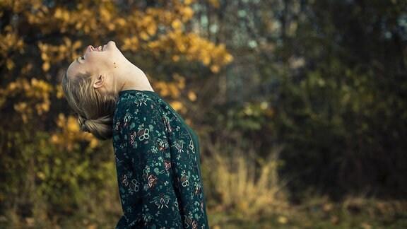 Junge Frau schaut zum Himmel, im Hintergrund ein Herbstwald.
