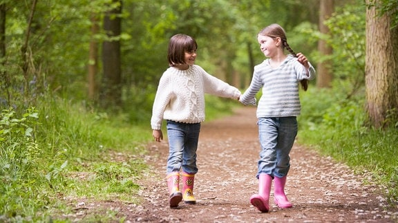 Zwei Mädchen spazieren durch den Wald.