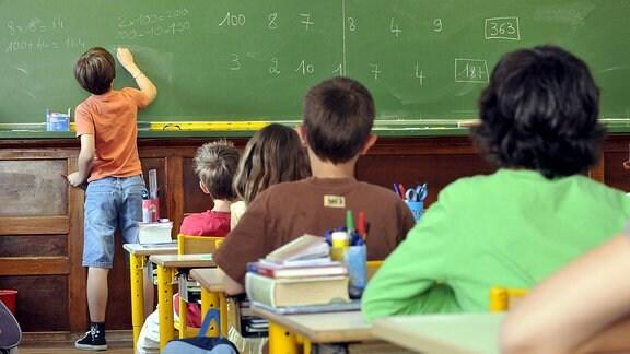 Ein Junge schreibt im Klassenzimmer an die Tafel.