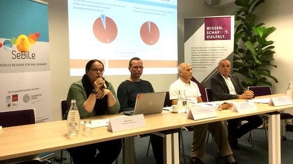 Eine Frau und drei Männer an einem Tisch während einer Pressekonferenz