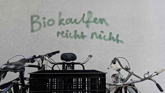 """Grafitto: """"Bio kaufen reicht nicht"""" steht an eine Wand geschrieben – davor teilweise sichtbar abgestellte Fahrräder"""