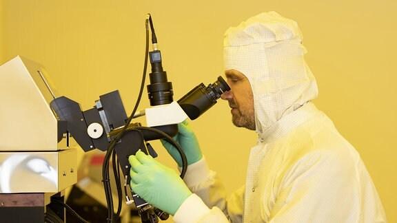 Ein Mann in Schutzkleidung sieht durch ein Mikroskop