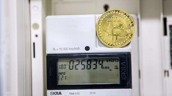Eine goldfarbene Bitcoin-Münz-Attrappe steht auf einem Stromzähler, der die Zahl der Kilowattstunden im Display anzeigt.
