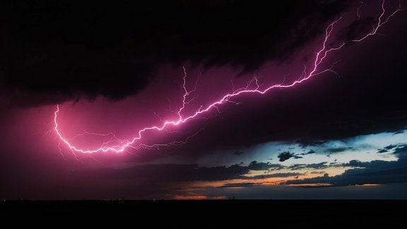 Ein pinker Blitz am dunklen Himmel