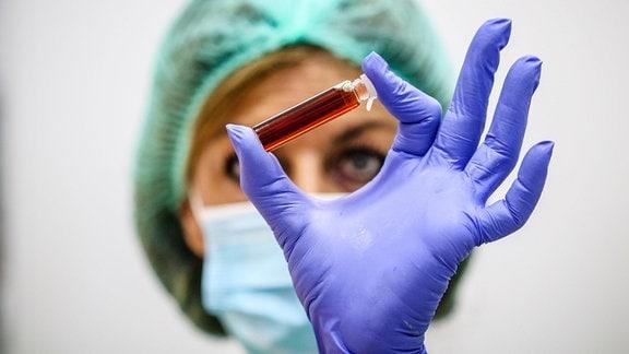 Laborantin hält Blutprobe