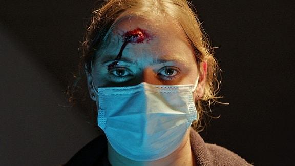 Eine junge Frau mit blutender Stirn