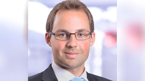 Mann mit Brille und stahlblauer Krawatte