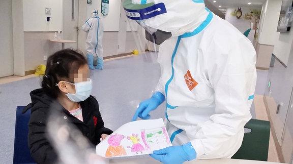 Ein mit dem Corona-Virus infiziertes Mädchen schenkt der Krankenschwester Yang Liu ein Bild.