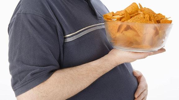 Ein Mann hält eine Schüssel mit Chips.