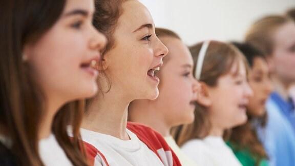 Drei hellhäutige Mädchen stehen nebeneinander und singen