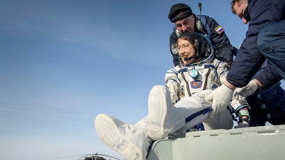 Astronautin Christina Koch ist auf der erde gelandet und steigt aus der Landekapsel.
