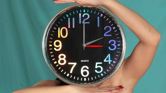 Eine Frau hält sich eine große Uhr vor das Gesicht