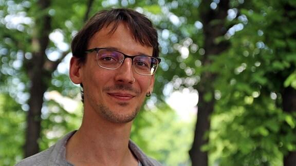 Porträtaufnahme eines jungen Wissenschaftlers mit kurzen braunen Haaren, Brille und Nasenpiercing vom Deutschen Zentrum für integrative Biodiversitätsforschung.