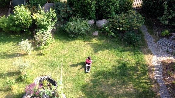 Eine Person sitzt auf dem Rasen inmitten eines Gartens und hält Ausschau. In den Händen hält sie einen Notizblock und Stift.