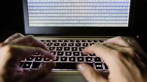 Hand einer Person, die auf Laptop schreibt.