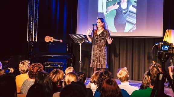 Reporterin Daniela Schmidt steht auf der kleinen Bühne im Kupfersaal in Leipzig und trägt ihr Stand-Up-Comedy-Stück vor.