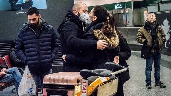 Auf einem Flughafen umarmen sich ein Mann und eine Frau zur Begrüßung. Beide tragen einen Mundschutz.