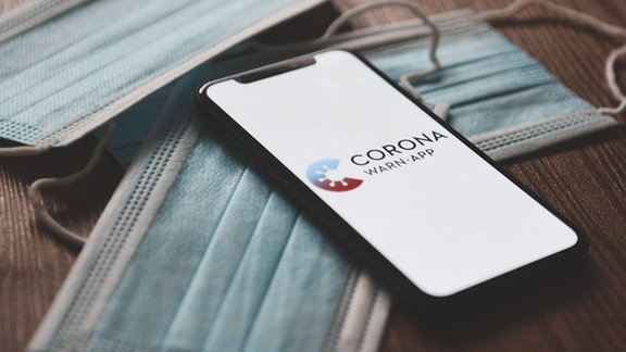 Corona-Warn-App, Das Logo der Corona-Warn-App auf einem Smartphone. Mithilfe der App werden Bürger benachrichtigt, sollten Sie sich in der Nähe eines am Coronavirus Erkrankten aufgehalten haben, wenn dieser die App ebenso installiert hatte und seine Erkrankung meldet.