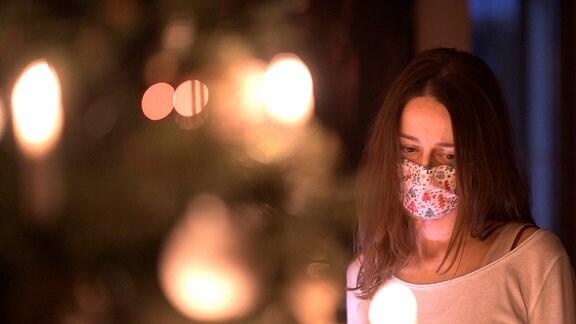 Eine Frau mit Mund-Nasenschutz-Maske schaut nachdenklich auf den leuchtenden Weihnachstbaum im Wohnzimmer