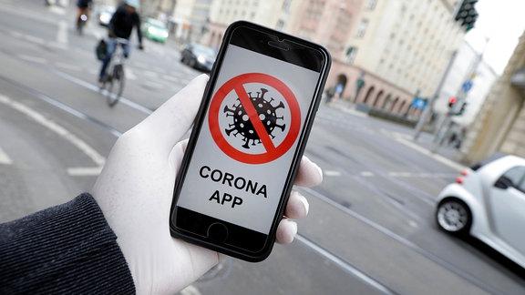 Bild eines durchgestrichenen Virus und Aufschrift Corona-App auf dem Display eines Smartphones